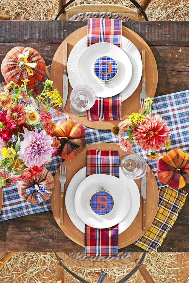 """<p>It doesn't get much cuter than these <a href=""""https://www.amazon.com/KINGSO-Stitch-Embroidery-Adjustable-Crosses/dp/B074H7R95F"""" target=""""_blank"""">embroidery hoop</a> place cards. Layered with fabric initials and plaid cotton, they're the ultimate table accessory for any fall dinner party.</p><p><strong>Make the Place Settings:</strong> Use a <a href=""""https://www.amazon.com/Darice-Wood-Embroidery-Hoop-3/dp/B001B9I2ZY"""" target=""""_blank"""">3-inch embroidery hoop</a> to frame <a href=""""https://www.amazon.com/Michael-Miller-EO-087-Collection-Multicolor/dp/B005GRFJIK"""" target=""""_blank"""">plaid fabric</a>. Iron on <a href=""""https://www.amazon.com/Camdon-Polyvinyl-Transfer-Letters-Orange/dp/B074PD6CHR"""" target=""""_blank"""">orange fabric initials</a> or affix with <a href=""""https://www.amazon.com/Mistyfuse-Misty-Yards-Fusible-Webbing/dp/B000PFPSJI"""" target=""""_blank"""">fusible webbing</a>.</p><p><a class=""""body-btn-link"""" href=""""https://www.amazon.com/Cotton-Craft-12-Pack-Construction/dp/B07M6NSGWX?tag=syn-yahoo-20&ascsubtag=%5Bartid%7C10050.g.1538%5Bsrc%7Cyahoo-us"""" target=""""_blank"""">SHOP PLAID NAPKINS</a></p>"""