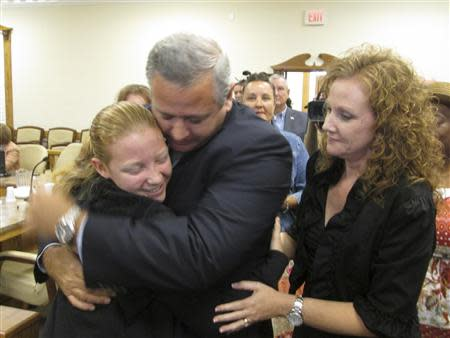 Suspended Liberty County Sheriff Nick Finch hugs his 16-year-old daughter Amber as his wife, Angela Finch (R), approaches after his acquittal on charges of official misconduct and falsifying official documents in Tallahassee, Florida October 31, 2013. REUTERS/Bill Cotterell