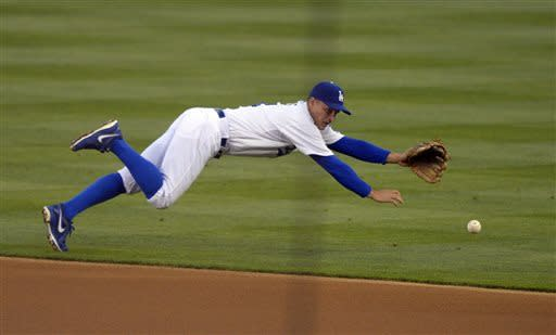 Los Angeles Dodgers second baseman Mark Ellis can't reach a ball hit for an RBI single by San Diego Padres' Yonder Alonso during the first inning of their baseball game, Tuesday, April 16, 2013, in Los Angeles. (AP Photo/Mark J. Terrill)