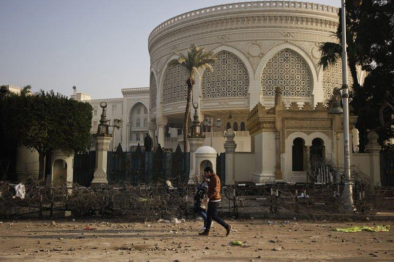 An Egyptian couple walks past a damaged barbed wire fence outside the presidential palace in Cairo on February 2, 2013
