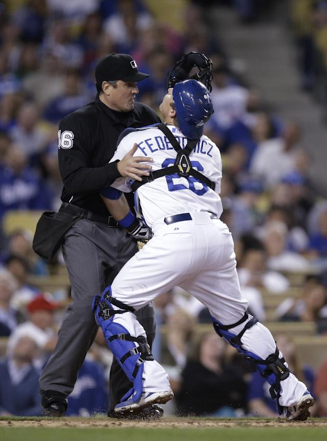 Los Angeles Dodgers catcher Tim Federowicz, right, collides with umpire Mike DiMuro as Federowicz tries to catch a foul ball hit by Philadelphia Phillies' Freddy Galvis during the fifth inning of a baseball game on Thursday, April 24, 2014, in Los Angeles. Galvis struck out on the at-bat. (AP Photo/Jae C. Hong)
