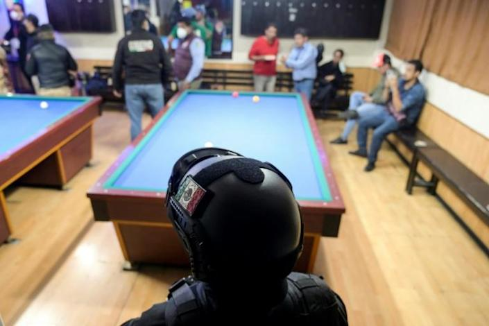 A Mexican police officer stands guard inside a billiard hall during a local government operation against illegal gatherings