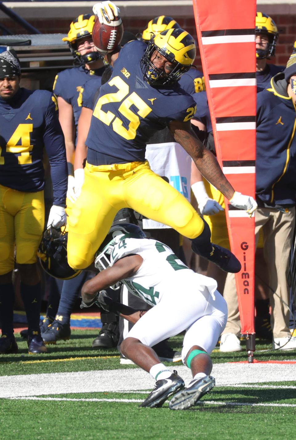 Michigan running back Hassan Haskins is tackled by Michigan State safety Tre Person at Michigan Stadium on Saturday, Oct. 31, 2020.