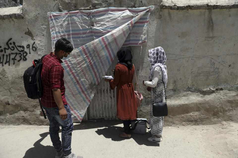 Health workers go door to door during a polio vaccination campaign in the old part of Kabul, Afghanistan, Tuesday, June 15, 2021. Gunmen on Tuesday targeted members of polio teams in eastern Afghanistan, killing some staffers, officials said. (AP Photo/Rahmat Gul)