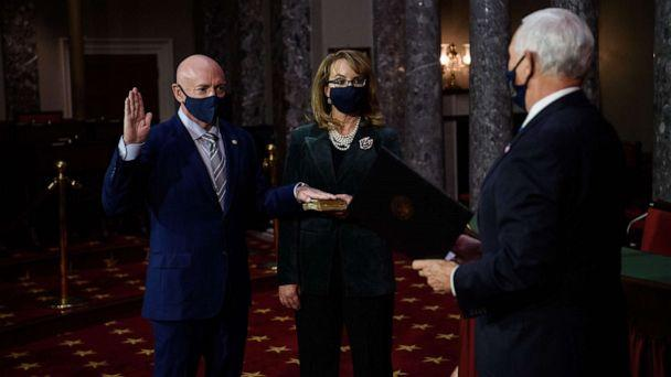 PHOTO: Democratic Senator from Arizona, Mark Kelly, with his wife, former Representative from Arizona Gabby Giffords, is sworn in by Vice President Mike Pence during a ceremonial re-enactment at the U.S. Capitol in Washington, Dec. 2, 2020. (Nicholas Kamm/Pool/AFP via Getty Images)
