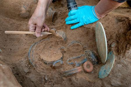 An archaeologist works in an Etruscan tomb containing a skeleton and dozens of objects in Aleria, in the east of the French Mediterranean island of Corsica, in this picture provided by INRAP (Institut National de Recherches Archeologique Preventives) on March 27, 2019.  Denis Gliksman/Inrap/HANDOUT via Reuters