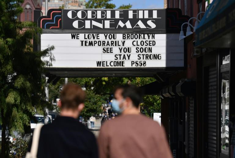 People walk past the Cobble Hill Cinemas movie theater on October 8, 2020 in New York City, which has been closed for months due to the coronavirus pandemic