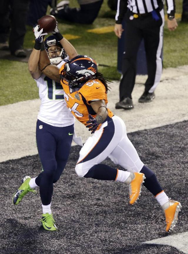Denver Broncos' Nate Irving (56) breaks up a pass to Seattle Seahawks' Jermaine Kearse (15) during the first half of the NFL Super Bowl XLVIII football game Sunday, Feb. 2, 2014, in East Rutherford, N.J. (AP Photo/Charlie Riedel)