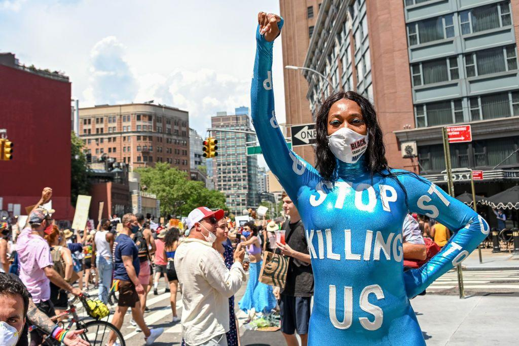<p>Singer Mila Jam poses in a jumpsuit that reads, 'stop killing us' at the Queer Liberation March for Black Lives & Against Police Brutality.</p>