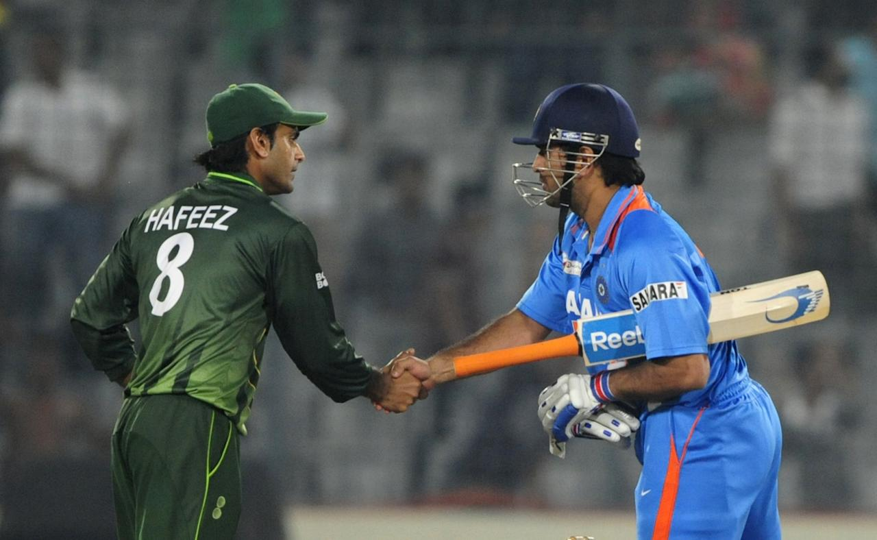 Indian captain Mahendra Singh Dhoni (R) shakes hands with Pakistan's Mohammad Hafeez (R) after India won the one day international (ODI) Asia Cup cricket match against Pakistan at The Sher-e-Bangla National Cricket Stadium in Dhaka on March 18, 2012. India defeated Pakistan by six wickets and Virat Kohli smashed a 148-ball 183 as India achieved the stiff 330-run target with 13 balls to spare in the day-night match, the first between the two teams since the World Cup semi-final at Mohali in March, 2011. AFP PHOTO/Munir uz ZAMAN (Photo credit should read MUNIR UZ ZAMAN/AFP/Getty Images)