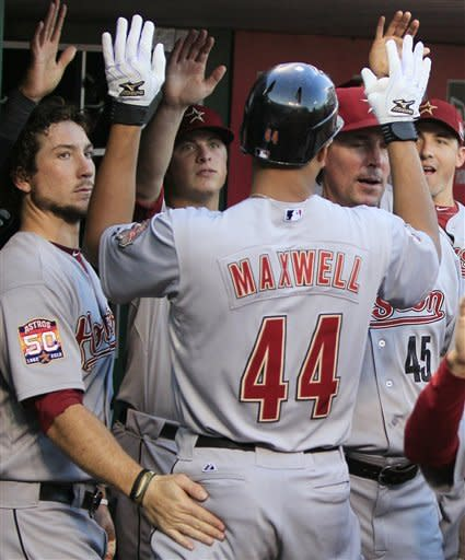 Houston Astros' Justin Maxwell (44) celebrates in the dugout after hitting a two-run home run in the first inning of a baseball game against the Cincinnati Reds, Friday, Sept. 7, 2012, in Cincinnati. (AP Photo/Al Behrman)