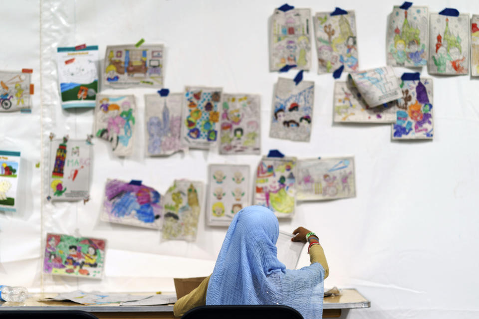 A child holds up a piece of artwork while drawing in a tent at Fort Bliss' Doña Ana Village, in New Mexico, where Afghan refugees are being housed, Friday, Sept. 10, 2021. The Biden administration provided the first public look inside the U.S. military base where Afghans airlifted out of Afghanistan are screened, amid questions about how the government is caring for the refugees and vetting them. (AP Photo/David Goldman)