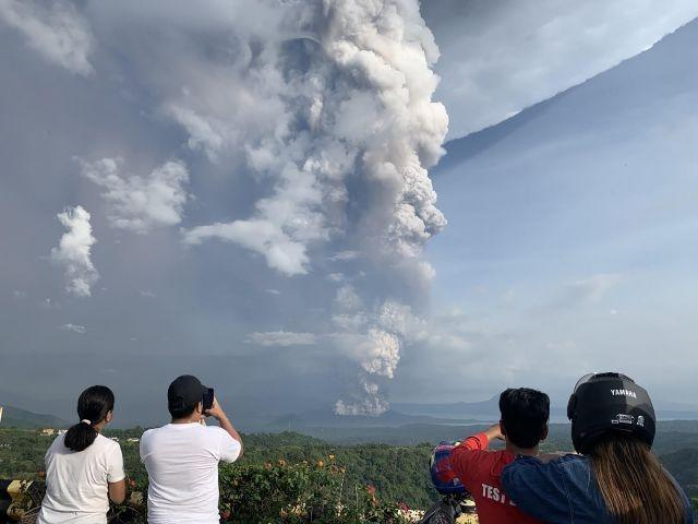 People take photos of a phreatic explosion from the Taal volcano as seen from the town of Tagaytay in Cavite province, southwest of Manila, on January 12, 2020