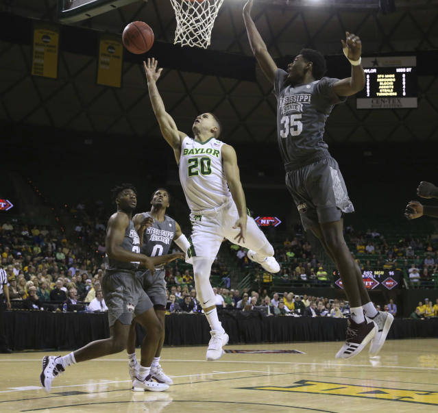 Baylor guard Manu Lecomte, left, scores past Mississippi State forward Aric Holman, right, during the first half of an NCAA college basketball game in the second round of the NIT tournament, Sunday, March 18, 2018, in Waco, Texas. (Michael Bancale/Waco Tribune-Herald via AP)
