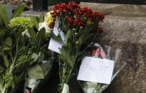 Flowers and other items are left by members of the public outside the gates of Windsor Castle, a day after the death of Britain's Prince Philip, in Windsor, England, Saturday, April 10, 2021. Britain's Prince Philip, the irascible and tough-minded husband of Queen Elizabeth II who spent more than seven decades supporting his wife in a role that mostly defined his life, died on Friday. (AP Photo/Frank Augstein)