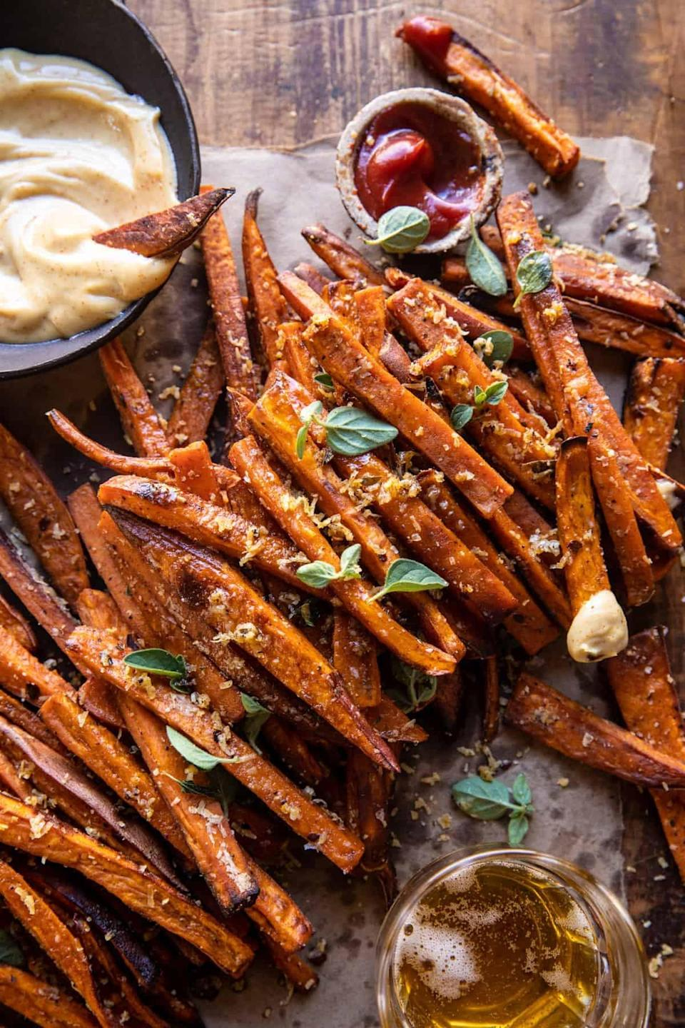 "<p>Make the most of sweet potatoes when you cook up these perfectly crunchy fries. Who can say no to warm potato slices with a rich and spicy aioli, anyway? Since this recipe makes six servings, you can cut it in half and enjoy enough fries for two people, and then some.</p> <p><strong>Get the recipe:</strong> <a href=""https://www.halfbakedharvest.com/garlic-parmesan-sweet-potato-fries/"" class=""link rapid-noclick-resp"" rel=""nofollow noopener"" target=""_blank"" data-ylk=""slk:garlic parmesan sweet potato fries with spicy aioli"">garlic parmesan sweet potato fries with spicy aioli</a></p>"