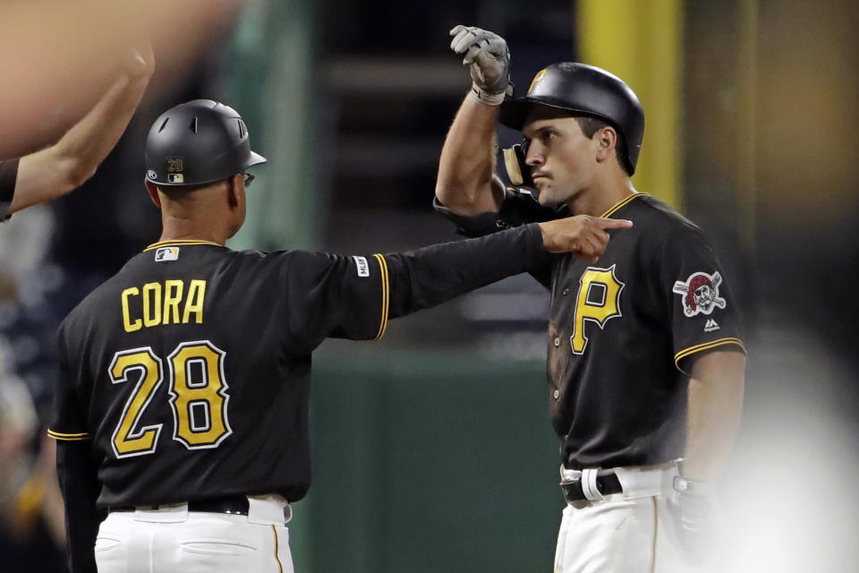 Pittsburgh Pirates' Adam Frazier, right, stands on third base next to coach Joey Cora and gestures to the dugout after driving in two runs with a triple off St. Louis Cardinals relief pitcher John Brebbia during the seventh inning of a baseball game in Pittsburgh, Friday, Sept. 6, 2019. (AP Photo/Gene J. Puskar)