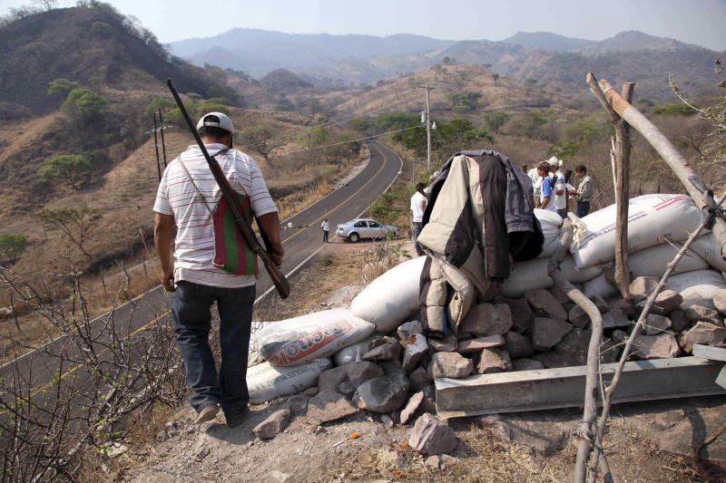 In this May 20, 2013 photo, armed men belonging to a local self-defense group patrol the entrance to the town of Buenavista, Mexico. Self-defense groups started to spring up in February to fight back the Knights Templar drug cartel which is extorting protection payments from cattlemen and lime growers, butchers and even marijuana growers. The federal government sees both the self-defense forces and the cartel as dangerous enemies. (AP Photo/Marco Ugarte)