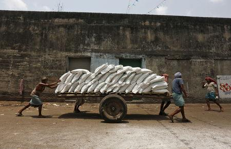 Labourers push a handcart loaded with sacks of sugar at a wholesale market in Kolkata