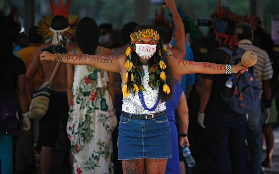 An indigenous woman wears protective mask reading Salles out, referring to Brazilian Environment Minister Ricardo Salles, during a protest against President Jair Bolsonaro's mining politics regarding indigenous lands, outside the Ministry of the Environment building in Brasilia - Sergio Lima/AFP