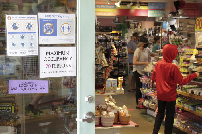 In this Thursday, May 28, 2020, photo tourists shop at Bruce's Candy Kitchen amid social distancing restrictions during the coronavirus outbreak in Cannon Beach, Ore. With summer looming, Cannon Beach and thousands of other small, tourist-dependent towns nationwide are struggling to balance fears of contagion with their economic survival in what could be a make-or-break summer. (AP Photo/Gillian Flaccus)