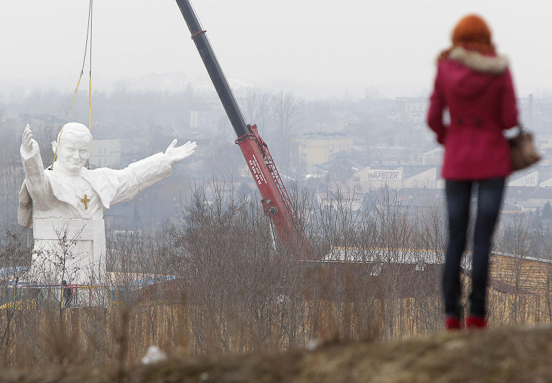 A woman looks at the  giant statue  of  late Pope John Paul II being readied for unveiling this weekend, in Czestochowa, Poland, Tuesday, April 9, 2013. The 13.8-meter (45.3-foot) white fiberglass figure will tower over the southern city of Czestochowa, home to Poland's most important Catholic pilgrimage site, Jasna Gora.  Funded by a private investor, the pontiff appears smiling and stretching his arms to the world.   (AP Photo/Czarek Sokolowski)