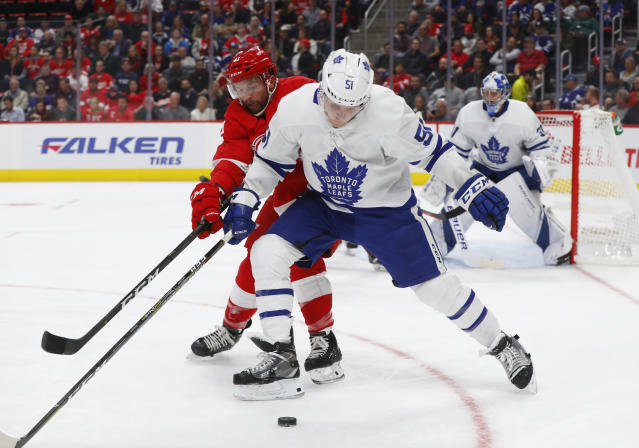 Toronto Maple Leafs defenseman Jake Gardiner (51) and Detroit Red Wings center Luke Glendening (41) compete for the puck during the second period of an NHL hockey game Thursday, Oct. 11, 2018, in Detroit. (AP Photo/Paul Sancya)