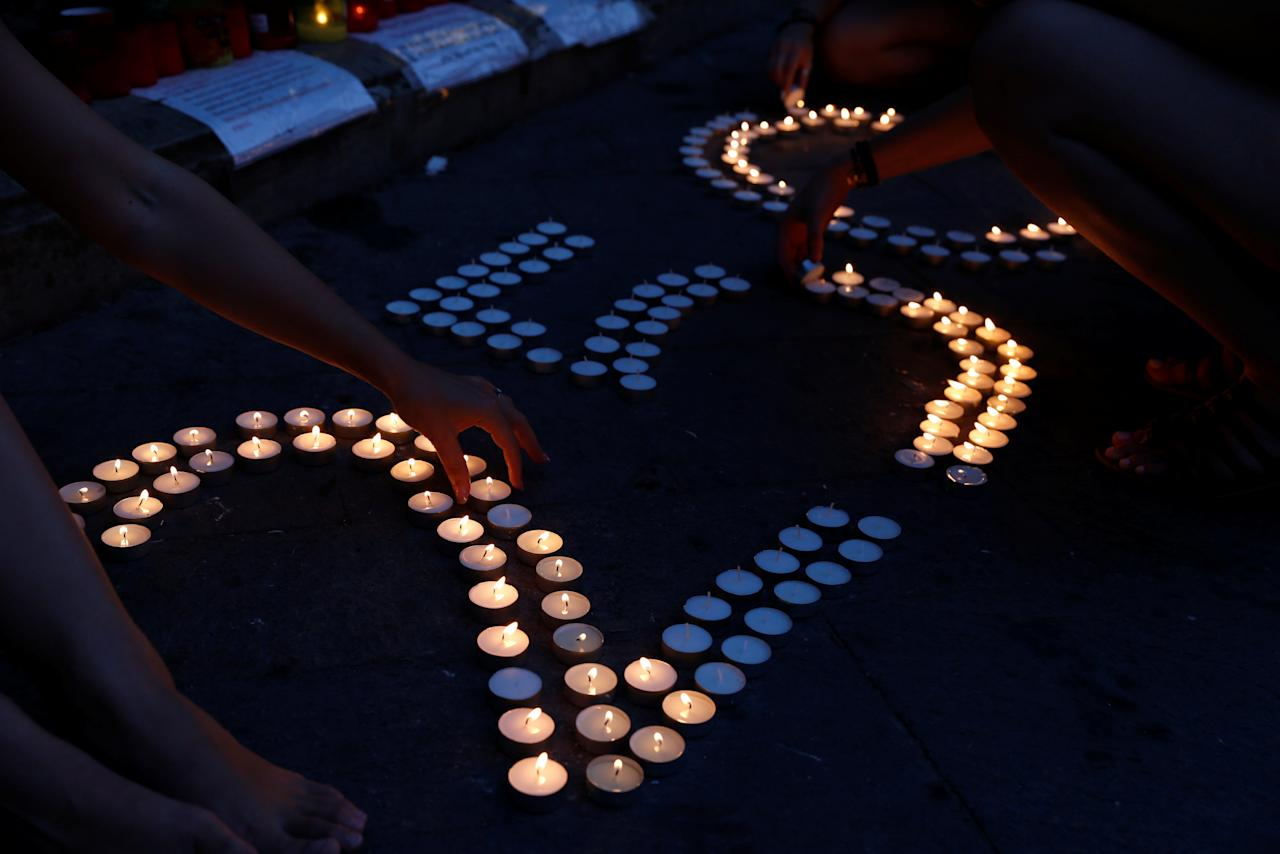Greek and Italian tourists help a lone activist placing and lighting candles to mark 250 days since the assassination of anti-corruption journalist Daphne Caruana Galizia at a makeshift memorial to her outside the Courts of Justice in Valletta, Malta June 23, 2018. REUTERS/Darrin Zammit Lupi