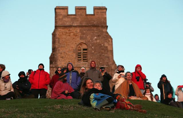 GLASTONBURY, ENGLAND - MAY 01: People sit and watch the sun rise as they join in a Beltane dawn celebration service in front of St. Michael's Tower on Glastonbury Tor on May 1, 2013 in Glastonbury, England. Although more synonymous with International Workers' Day, or Labour Day, May Day or Beltane is celebrated by druids and pagans as the beginning of summer and the chance to celebrate the coming of the season of warmth and light. Other traditional English May Day rites and celebrations include Morris dancing and the crowning of a May Queen with celebrations involving a Maypole. (Photo by Matt Cardy/Getty Images)