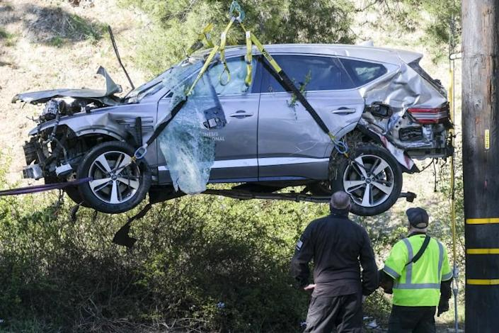 A crane is used to lift a vehicle following a rollover accident involving golfer Tiger Woods
