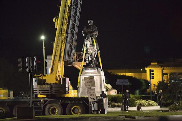 <p>Workers in protective gear attach straps to the statue of Confederate Gen. P.G.T. Beauregard as it is prepared for removal from the entrance to City Park in New Orleans, March 17, 2017. The city council voted to remove the monument and three other Confederate and white supremacist monuments in Dec. 2015. (Photo: Scott Threlkeld/AP) </p>