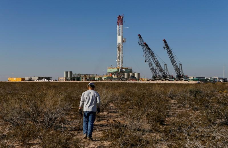 FILE PHOTO: An oil worker walks towards a drill rig after placing ground monitoring equipment in the vicinity of the underground horizontal drill in Loving County