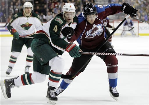 Minnesota Wild defenseman Clayton Stoner (4) collides with Colorado Avalanche right wing David Jones as they skate for the puck in the first period of their NHL hockey game on Tuesday, Jan. 24, 2012, in Denver. (AP Photo/Joe Mahoney)