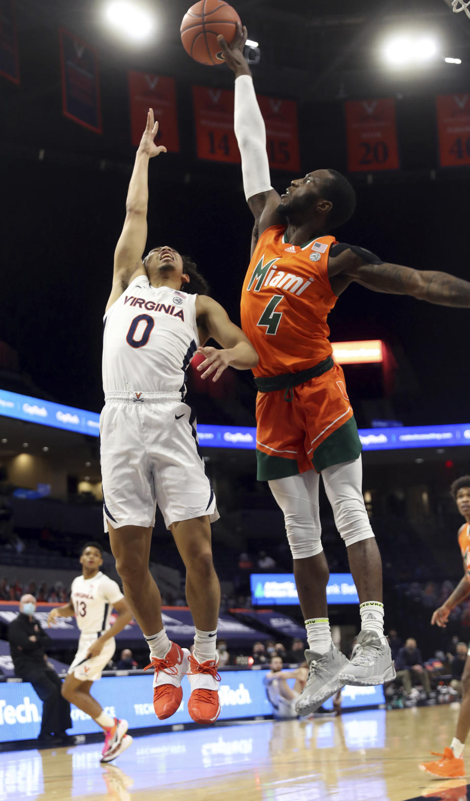 Miami guard Elijah Olaniyi (4) blocks the shot of Virginia guard Kihei Clark (0) during an NCAA college basketball game Monday in Charlottesville, Va. (Andrew Shurtleff/The Daily Progress via AP, Pool)