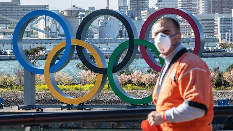 A man wearing a face mask, pictured here walking near the Olympic Rings in Tokyo, Japan.