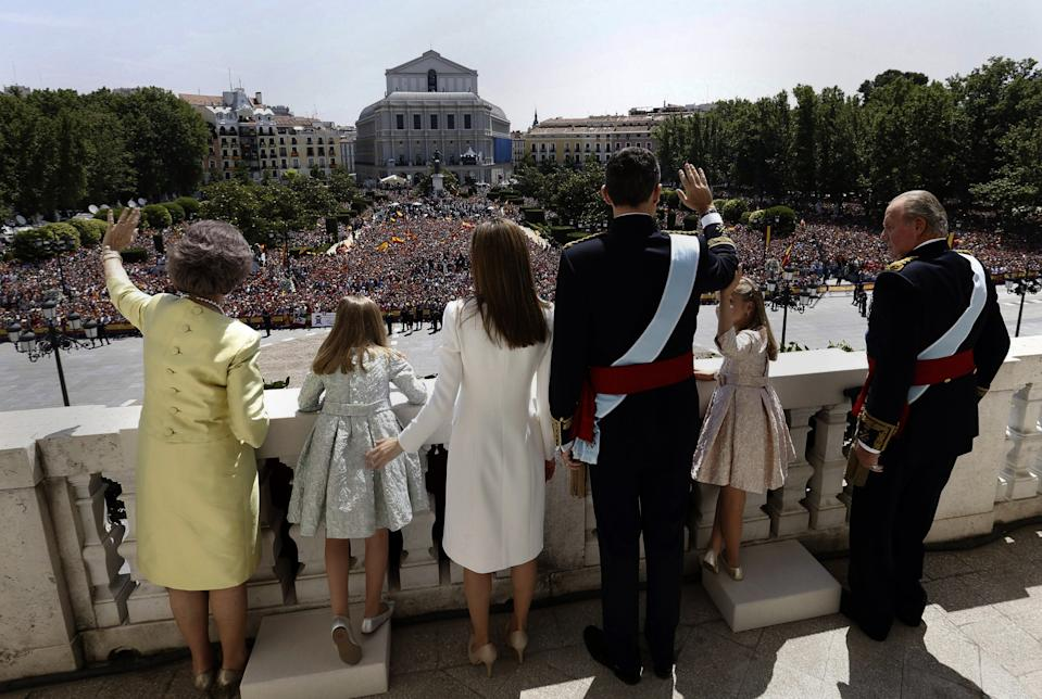 Spain's newly crowned King Felipe VI, third right, his father Juan Carlos, right, his mother Sofia, left, his wife Spain's Queen Letizia, third left, and his daughters Spain's Princess Leonor, second right, and Spain's Princess Sofia, second left, wave from a balcony of the Royal Palace in Madrid, Spain, Thursday June 19, 2014. Felipe's father Juan Carlos, who reigned for four decades, stepped down after signing an abdication law Wednesday so that younger royal blood can rally a country beset by economic problems, including an unemployment rate of 25 percent. (AP Photo/Javier Lizon, Pool)