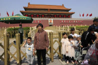 A child makes a gesture and winks as he poses for photos in front of Tiananmen Gate in Beijing on May 3, 2021. China's population growth is falling closer to zero as fewer couples have children, the government announced Tuesday, May 11, 2021, adding to strains on an aging society with a shrinking workforce. (AP Photo/Ng Han Guan)