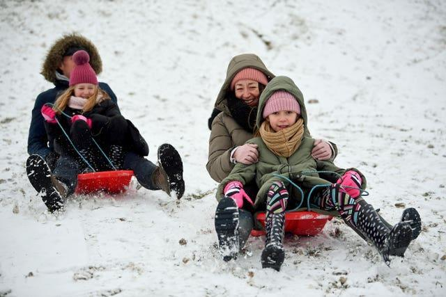 A group of people ride sledges in the snow in Essex