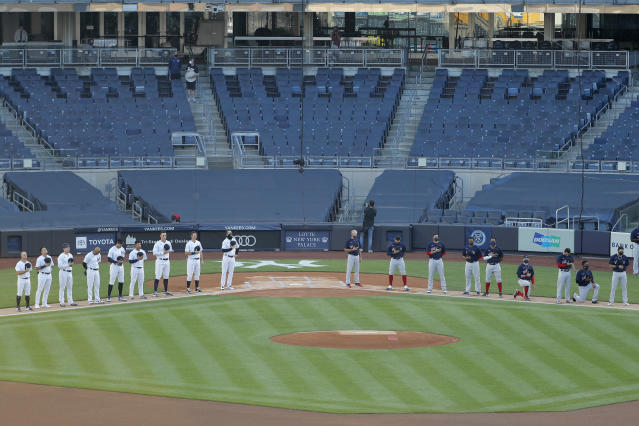 The New York Yankees, left, and the Boston Red Sox line up for the national anthem before the baseball game at Yankee Stadium, Friday, July 31, 2020, in New York. (AP Photo/Seth Wenig)