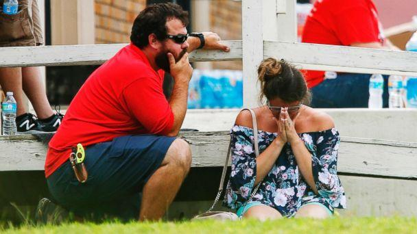 PHOTO: A woman prays in the grass outside the Alamo Gym where parents wait to reunite with their kids following a shooting at Santa Fe High School, May 18, 2018, in Santa Fe, Texas. (Michael Ciaglo/Houston Chronicle via AP)