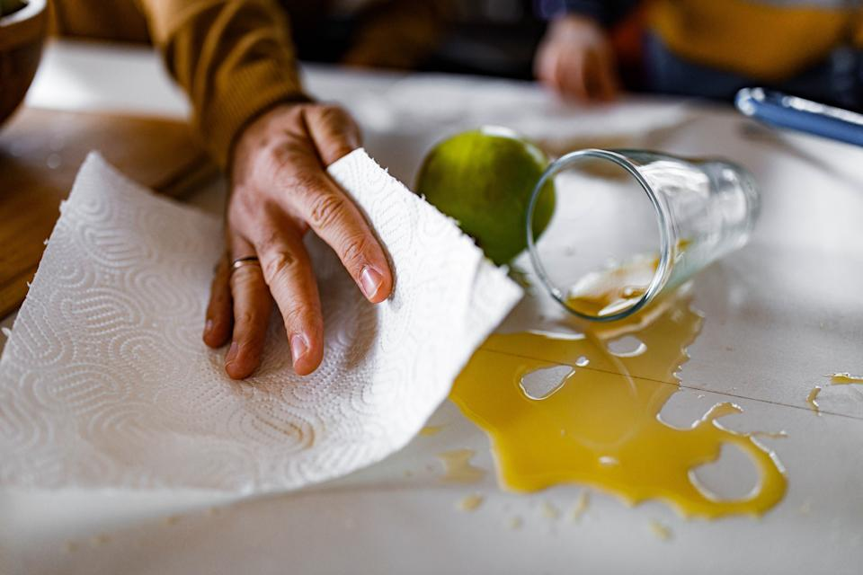 Close up of unrecognizable man cleaning spilled juice from the table.