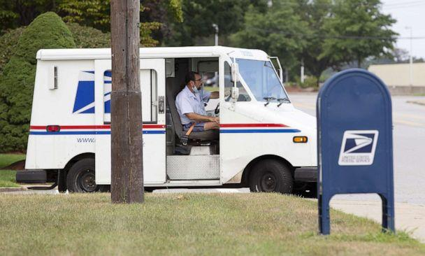 PHOTO: A United States Postal Service mail carrier drives his vehicle past a collection box in Woburn, Mass., August 17, 2020. (CJ Gunther/EPA via Shutterstock, FILE)