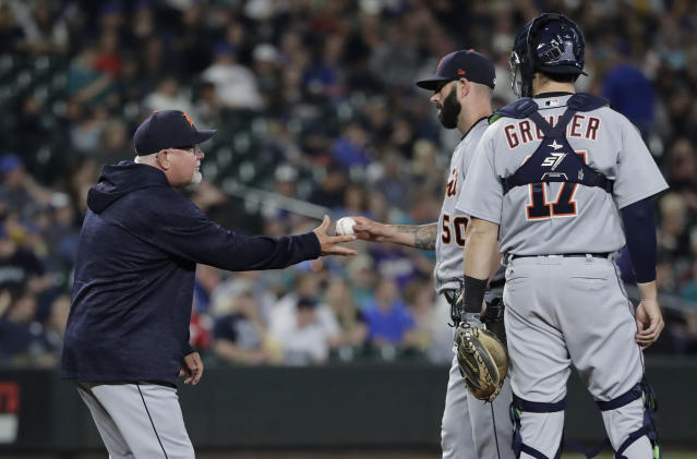 Detroit Tigers starting pitcher Mike Fiers, second from right, is pulled from a baseball game against the Seattle Mariners by manager Ron Gardenhire, left, as catcher Grayson Greiner watches during the sixth inning, Saturday, May 19, 2018, in Seattle. (AP Photo/Ted S. Warren)