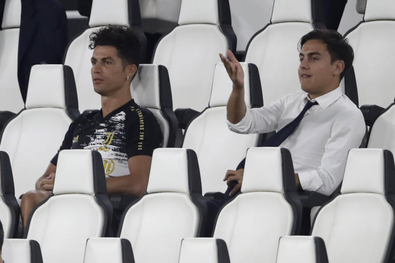 Juventus' Cristiano Ronaldo, left, and Juventus' Paulo Dybala gesture as attend a Serie A soccer match between Juventus and Roma, at the Allianz stadium in Turin, Italy, Saturday, Aug.1, 2020. (AP Photo/Luca Bruno)