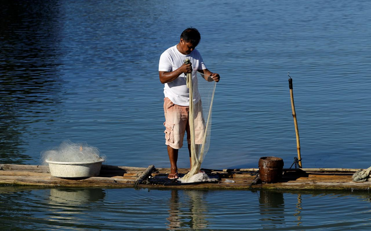 A resident arranges his net as he fishes in shallow waters near the shore in San Fernando, La Union, in northern Philippines September 25, 2016.   REUTERS/Czar Dancel