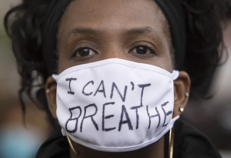 A woman attends a demonstration calling for justice for George Floyd in Montreal. Floyd died after he was pinned at the neck by a Minneapolis police officer. Source: AP