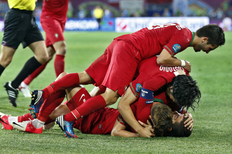 Portuguese players celebrate the second goal during the Euro 2012 soccer championship Group B match between Portugal and the Netherlands in Kharkiv, Ukraine, Sunday, June 13, 2012. (AP Photo/Armando Franca)