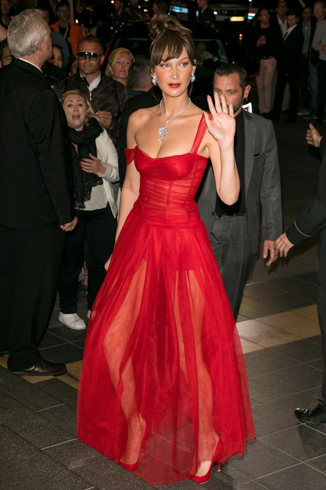 <p>Bella Hadid was follwoing along the same vein in this red Cinderella style dress with a sheer skirt. Photo: Getty </p>