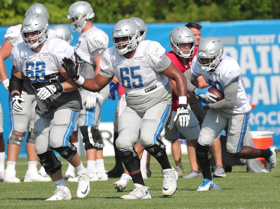 Joe Dahl (66) and Tyrell Crosby (65) block as Detroit Lions quarterback Matthew Stafford hands off to Kerryon Johnson during training camp at the facility in Allen Park, Thursday, August 27, 2020.
