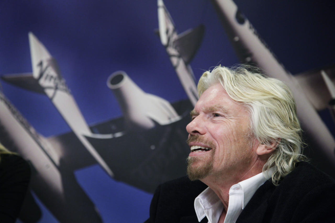 """Richard Branson, founder of the Branson Group, talks during an interview in his company's office, Thursday, Dec. 1, 2011 in New York. Branson is promoting his book, """"Screw Business as Usual."""" On the wall is a photograph of White Knight II, an aircraft built by Virgin Galactic. (AP Photo/Mark Lennihan)"""